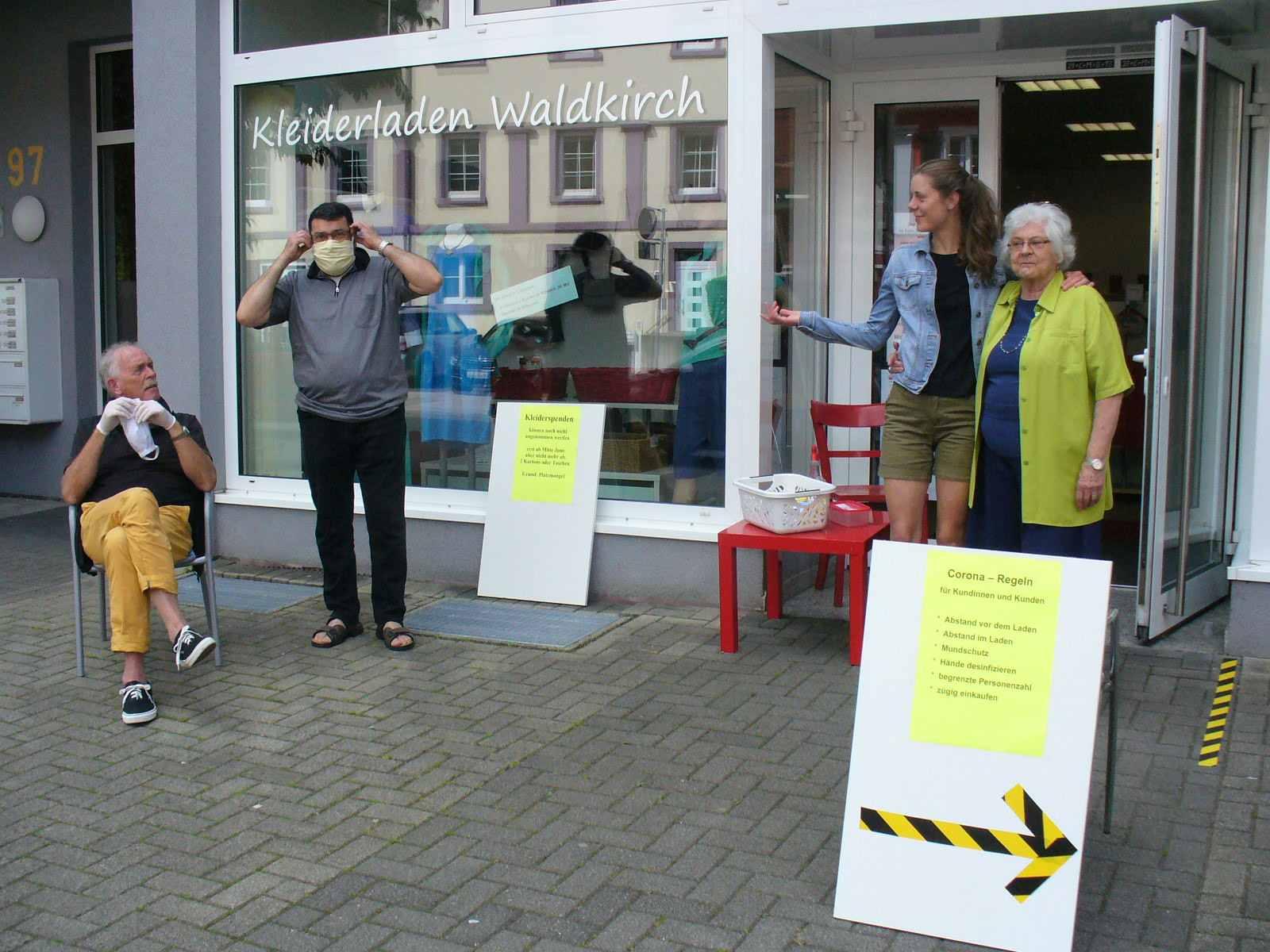 Vor dem Laden befinden sich vier Personen, die teilweise Mund-Nasen-Schutz-Masken tragen. Zudem sind Hinweisschilder zu den Corona- und Kleiderspendenregeln aufgestellt und es befinden sich Markierungen auf einem Schild und dem Boden.